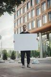 Jeune homme attirant tenant la toile vide et regardant la visionneuse Front View Image stock