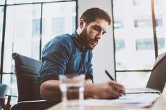 Jeune homme attirant travaillant au bureau ensoleillé de grenier sur l'ordinateur portable tout en se reposant à la table en bois Image libre de droits