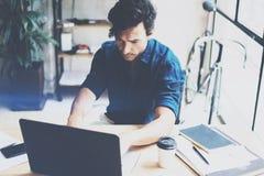 Jeune homme attirant travaillant au bureau ensoleillé sur l'ordinateur portable tout en se reposant à la table en bois L'homme d' Photo stock