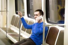 Jeune homme au téléphone portable dans le métro photo libre de droits