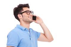 Jeune homme au téléphone regardant loin Image libre de droits