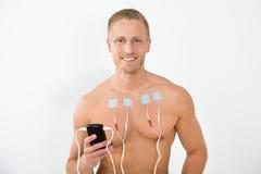 Jeune homme avec des électrodes sur le coffre Image stock