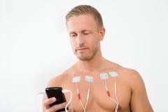 Jeune homme avec des électrodes sur le coffre Photographie stock