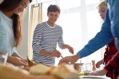 Jeune homme avec des amis mettant le Tableau de dîner Image stock
