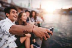 Jeune homme avec des amis prenant le selfie par le lac Photos libres de droits