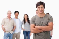 Jeune homme avec des bras pliés et des amis derrière lui Image stock