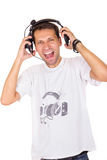 Jeune homme avec des cris d'écouteurs Photographie stock