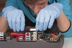 Jeune homme avec des gants installant le module de mémoire du Ram DDR4 dans la fente Photographie stock