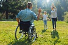 Jeune homme avec des incapacités ondulant le bonjour à sa famille Photo stock