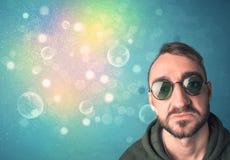 Jeune homme avec des lunettes de soleil et des lumières colorées de bokeh Photo stock