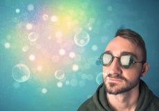 Jeune homme avec des lunettes de soleil et des lumières colorées de bokeh Photos libres de droits