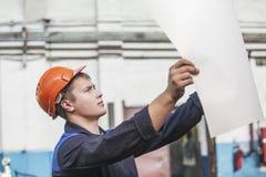 Jeune homme avec des modèles travaillant à une vieille usine pour l'inst image libre de droits