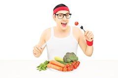 Jeune homme avec des verres mangeant des légumes photographie stock