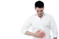 Jeune homme avec douleur d'estomac intense Photographie stock libre de droits