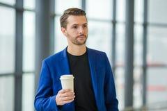 Jeune homme avec du café à l'intérieur dans l'aéroport tout en attendant l'embarquement Veste de port de costume de jeune garçon  Photos libres de droits