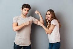 Jeune homme avec du charme montrant le biceps à son amie stupéfaite Photographie stock