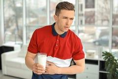 Jeune homme avec l'allergie de laiterie tenant le verre de lait photographie stock