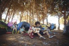 Jeune homme avec l'ami féminin jouant la guitare au terrain de camping Photo libre de droits