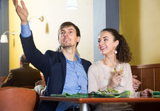 Jeune homme avec l'amie parlant dans la table de restaurant Images stock