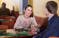 Jeune homme avec l'amie parlant dans la table de restaurant Image stock