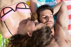 Jeune homme avec l'amie se trouvant sur la serviette à la plage Photos stock
