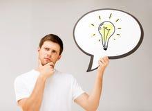Jeune homme avec l'ampoule dans la bulle des textes Photos stock