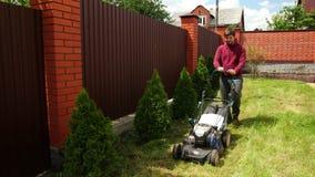 Jeune homme avec l'herbe de fauchage de barbe avec la tondeuse à gazon, arrière-cour, après-midi clips vidéos