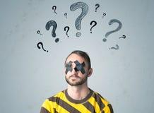 Jeune homme avec l'oeil collé et les symboles de point d'interrogation Photographie stock libre de droits