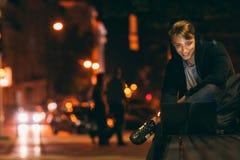 Jeune homme avec l'ordinateur portable dans la ville de nuit Images libres de droits