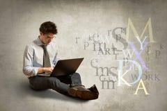 Jeune homme avec l'ordinateur portatif Photographie stock libre de droits