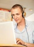 Jeune homme avec l'ordinateur portatif et les écouteurs Photo stock