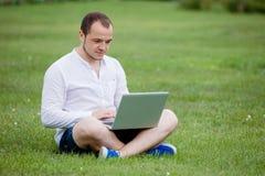 Jeune homme avec l'ordinateur portatif extérieur images libres de droits