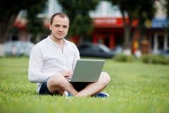 Jeune homme avec l'ordinateur portatif extérieur image stock