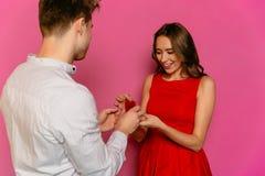 Jeune homme avec la bague de fiançailles faisant la proposition à sa jolie amie Photographie stock