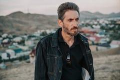 Jeune homme avec la barbe contre le contexte des montagnes Photo libre de droits