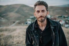 Jeune homme avec la barbe contre le contexte des montagnes Photographie stock