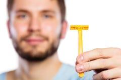 Jeune homme avec la barbe montrant la lame de rasoir Photos stock
