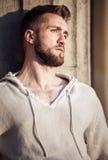 Jeune homme avec la barbe se penchant contre un mur image stock