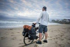 Jeune homme avec la bicyclette emballée sur la plage Photos libres de droits