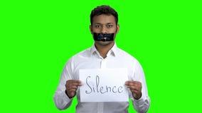 Jeune homme avec la bouche attachée du ruban adhésif sur l'écran vert clips vidéos