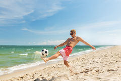 Jeune homme avec la boule jouant le football sur la plage Photo libre de droits