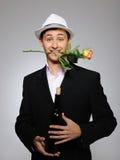 Jeune homme avec la bouteille rose de fleur et de vigne Images stock