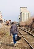 Jeune homme avec la caisse de guitare à disposition partant par chemins de fer blanc d'isolement de vue arrière Images libres de droits