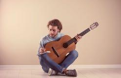 Jeune homme avec la chanson de composition de guitare acoustique près du mur images stock