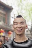 Jeune homme avec la coupe de cheveux de Mohawk souriant regardant l'appareil-photo Photographie stock