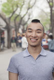Jeune homme avec la coupe de cheveux de Mohawk souriant regardant l'appareil-photo Photo stock