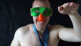 Jeune homme avec la danse nue de torse dans un masque drôle banque de vidéos