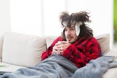 Jeune homme avec la grippe et la fièvre Photographie stock libre de droits