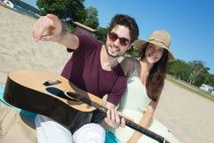 Jeune homme avec la guitare et l'amie sur la plage Photo libre de droits