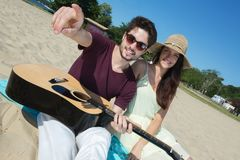 Jeune homme avec la guitare et l'amie sur la plage Photo stock